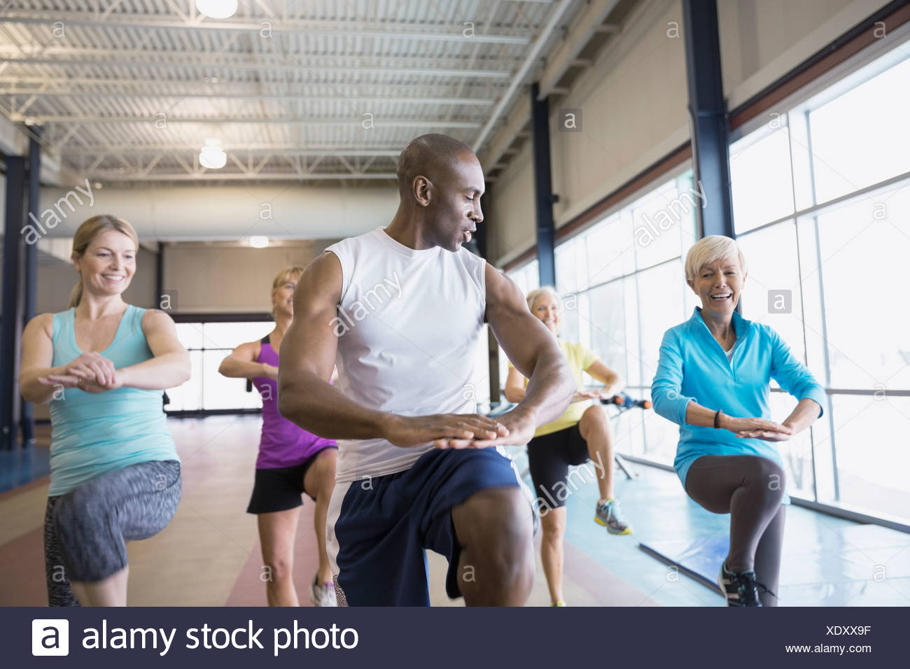 Personal trainer guiding women at gym - Stock Image