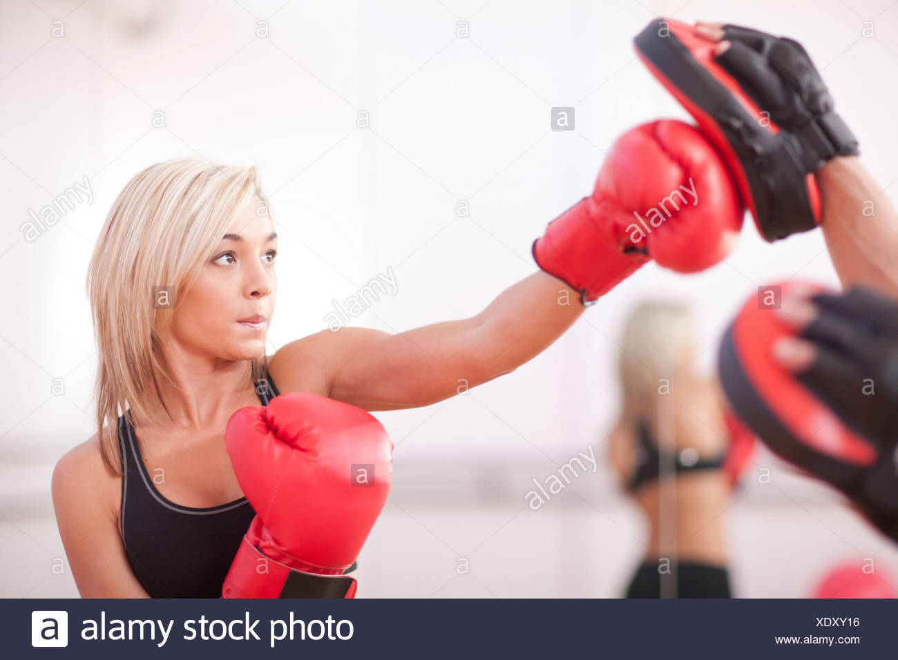 Young woman training in boxing gloves - Stock Image