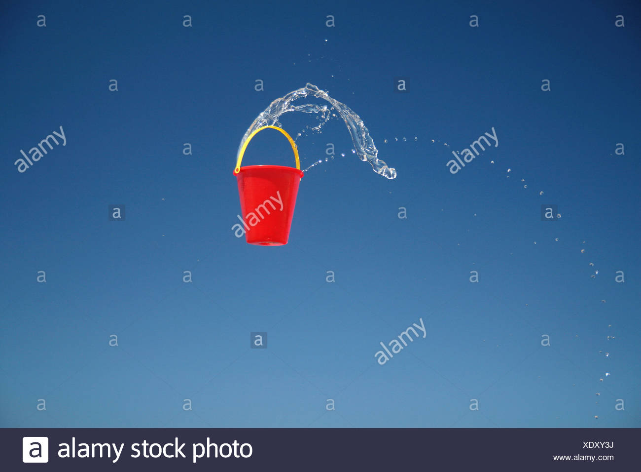 red bucket with water splashing out - Stock Image