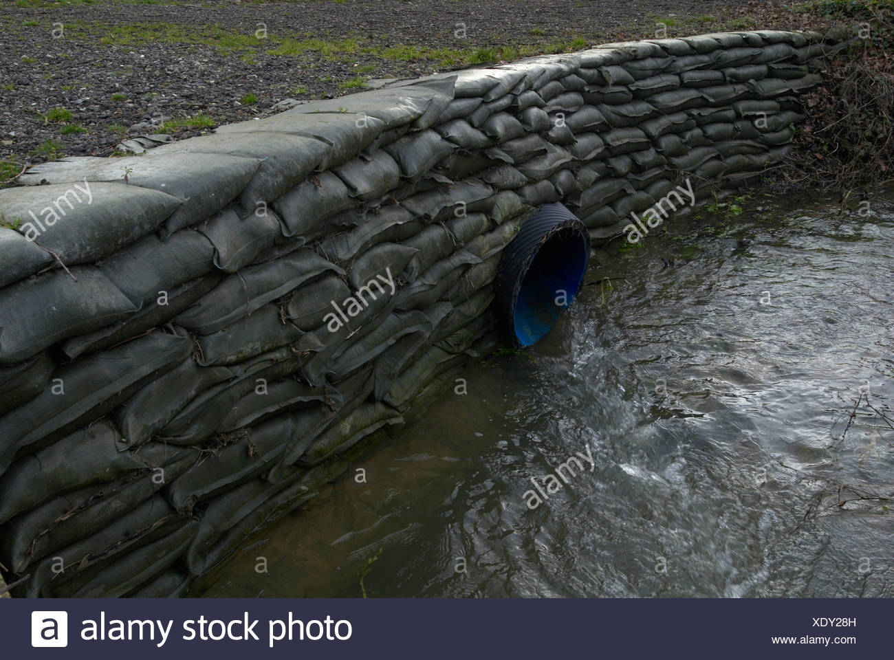 Pipe draining water into river - Stock Image