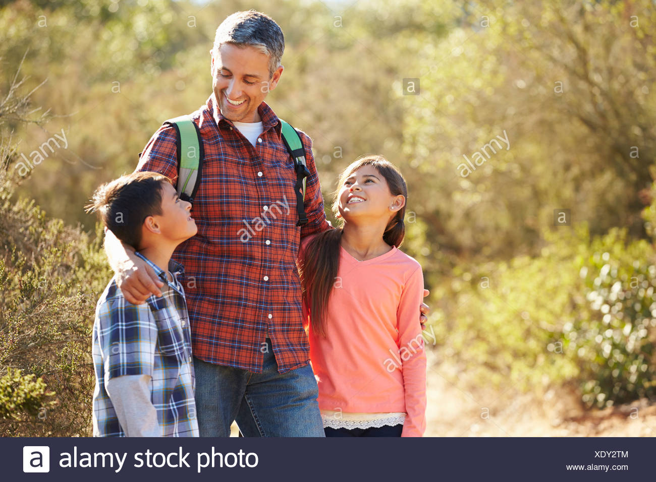 Father And Children Hiking In Countryside Wearing Backpacks - Stock Image