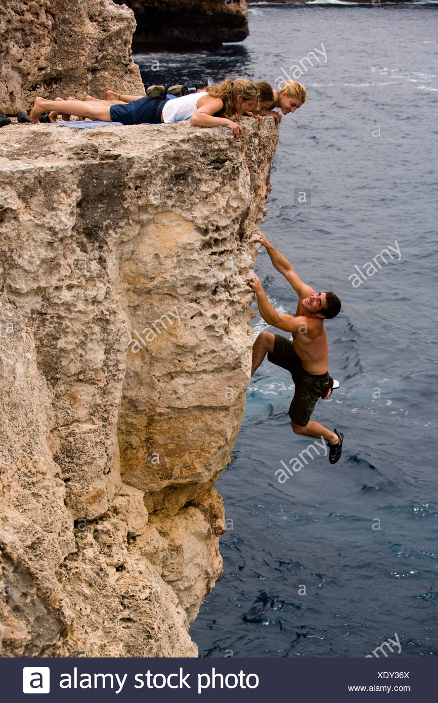 Three women watch a man deep water soloing / rock climbing on a cliff. Stock Photo