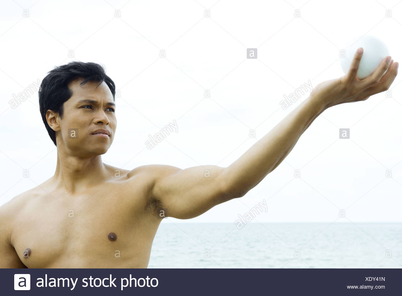 Man at the beach with arm raised, looking at ball in hand, close-up - Stock Image