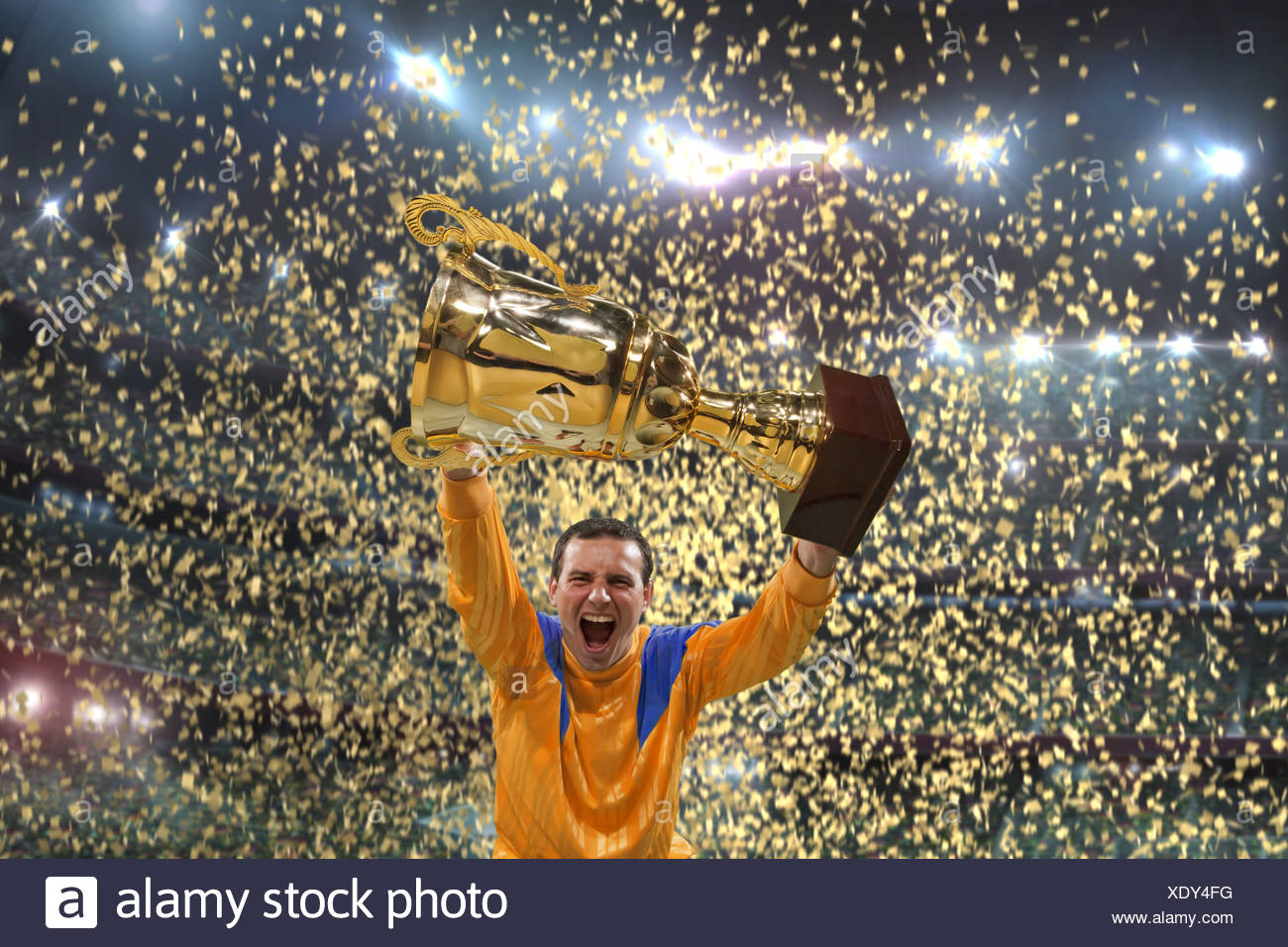 Football player holding up trophy, cheering, winner, winning, confetti, football stadium - Stock Image