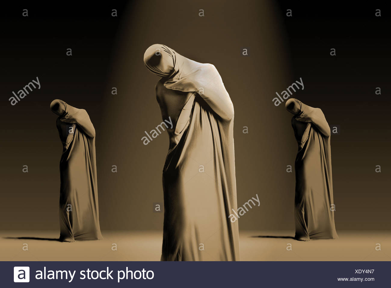 Three dancers wrapped in fabric standing with their heads cocked - Stock Image
