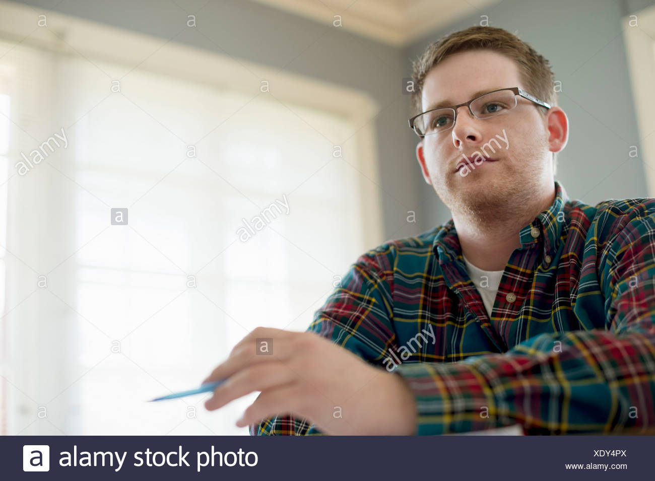 University student wearing glasses and checked shirt - Stock Image