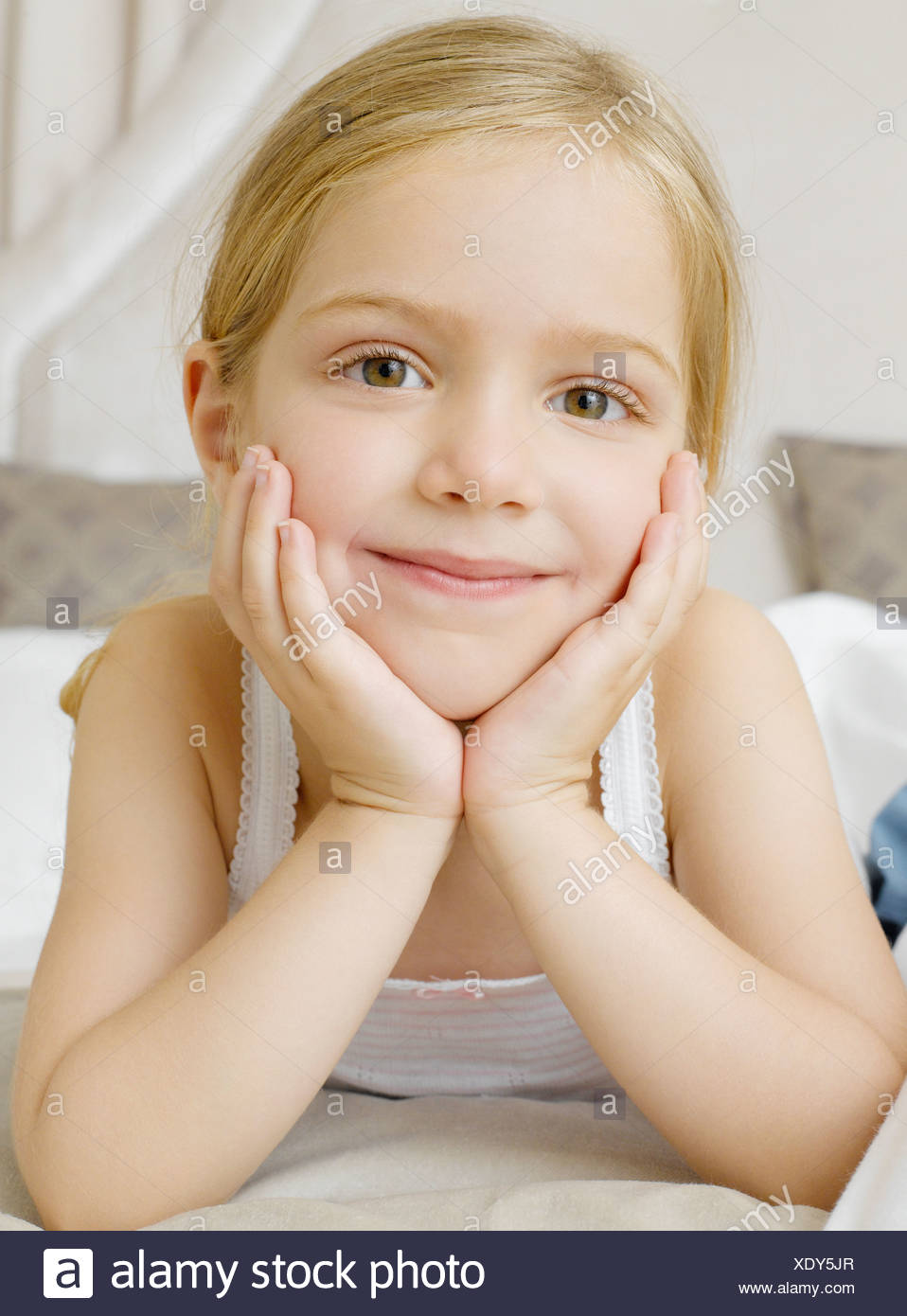 A young girl lying on her stomach cupping her face with her hands - Stock Image