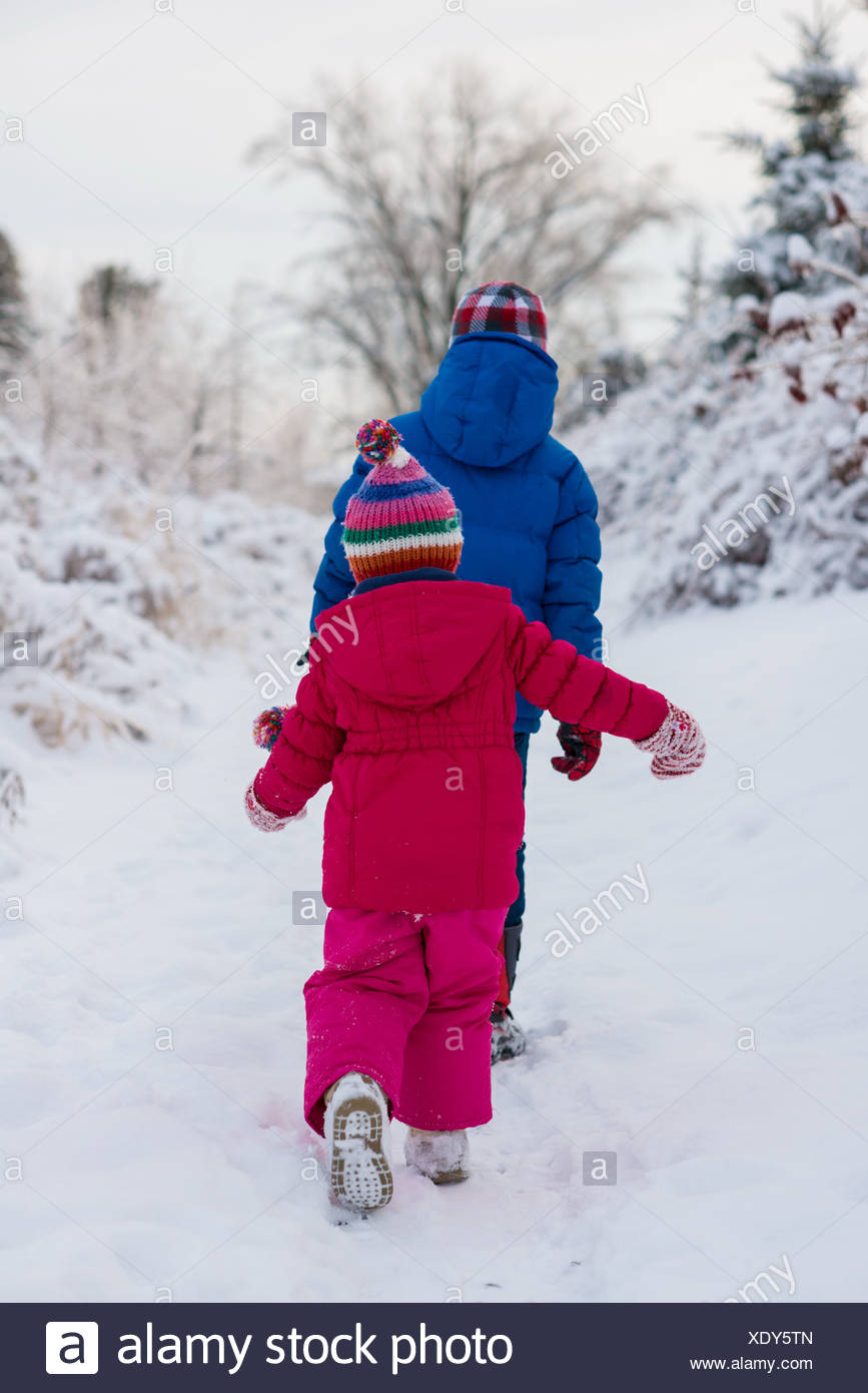 Brother and sister walking in snow - Stock Image