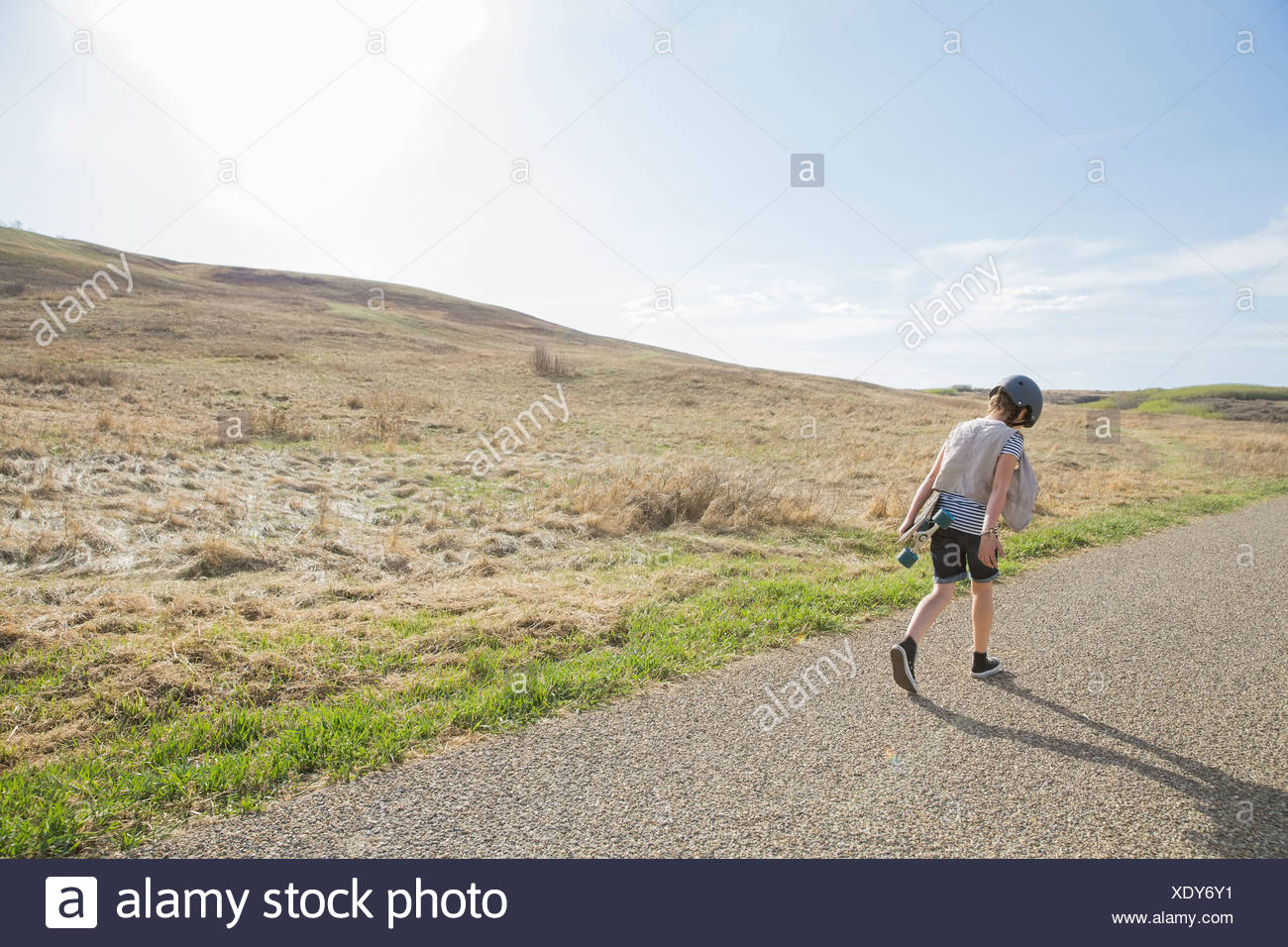 Rear view of girl walking on road with skateboard - Stock Image