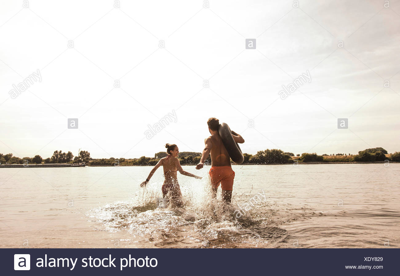 Young couple running with inner tube in river - Stock Image