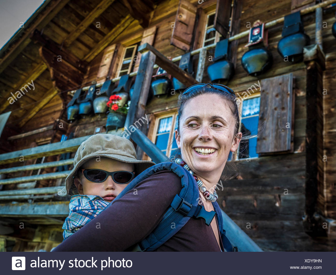 Woman giving child a piggyback ride, Bodme Alp, Gstaad, Canton of Bern, Switzerland - Stock Image