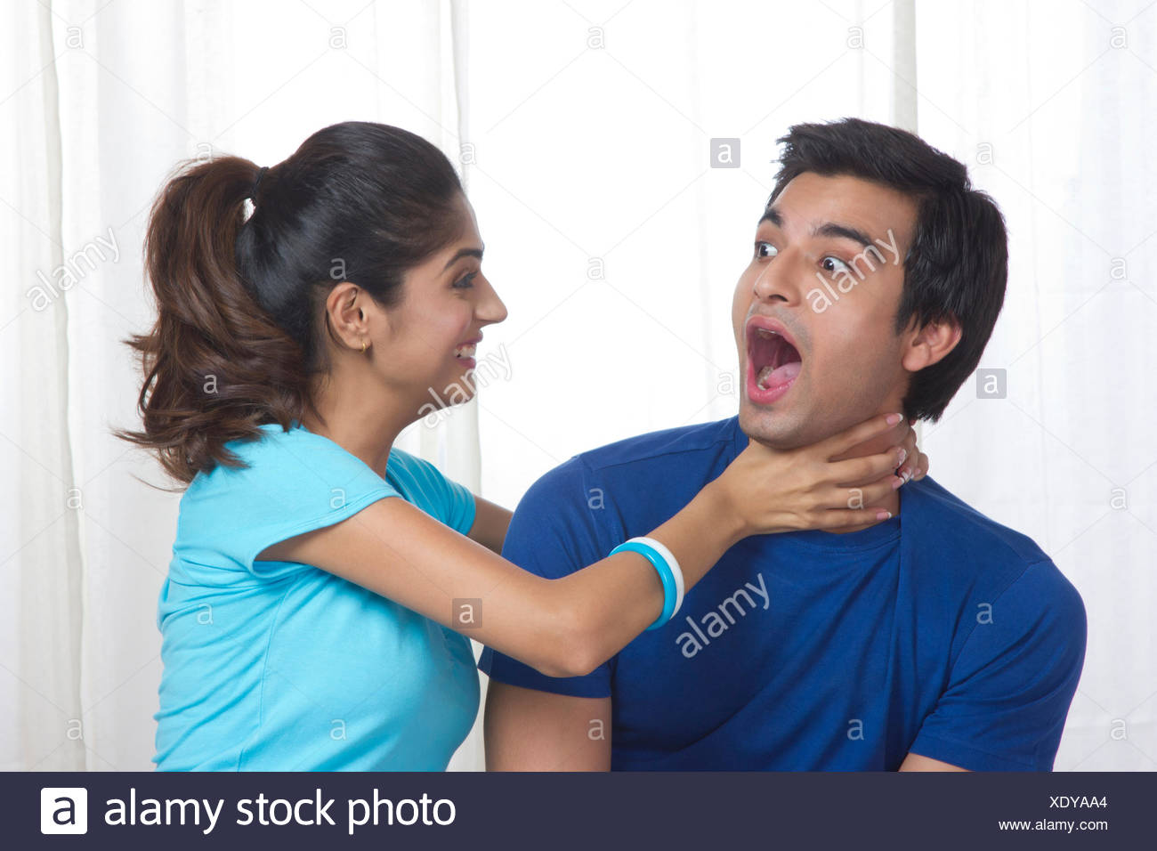 Playful young woman gripping man's neck at home - Stock Image