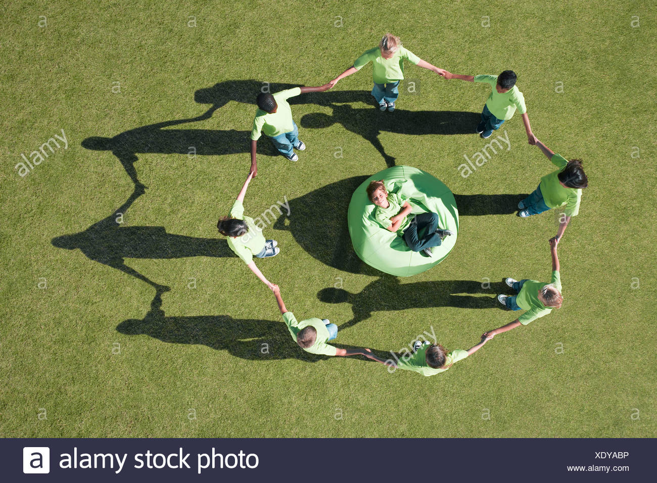 Group of children holding hands around boy in bean bag - Stock Image