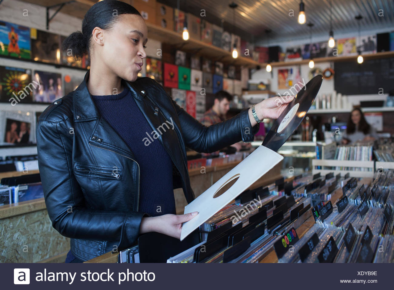 Young woman in a record store. - Stock Image