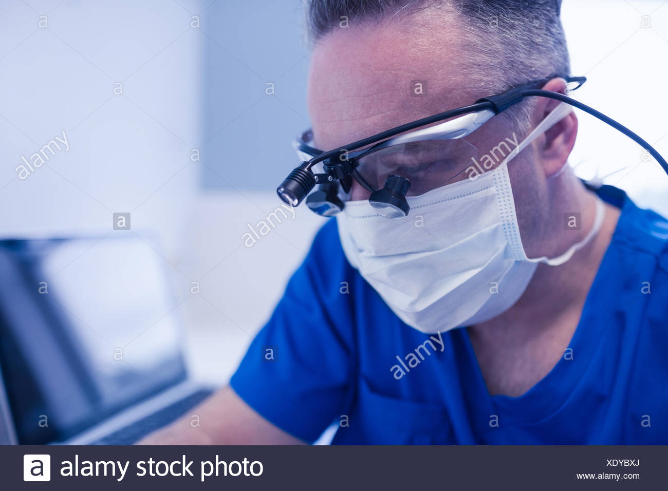 Concentrated male dentist with dental loupes - Stock Image