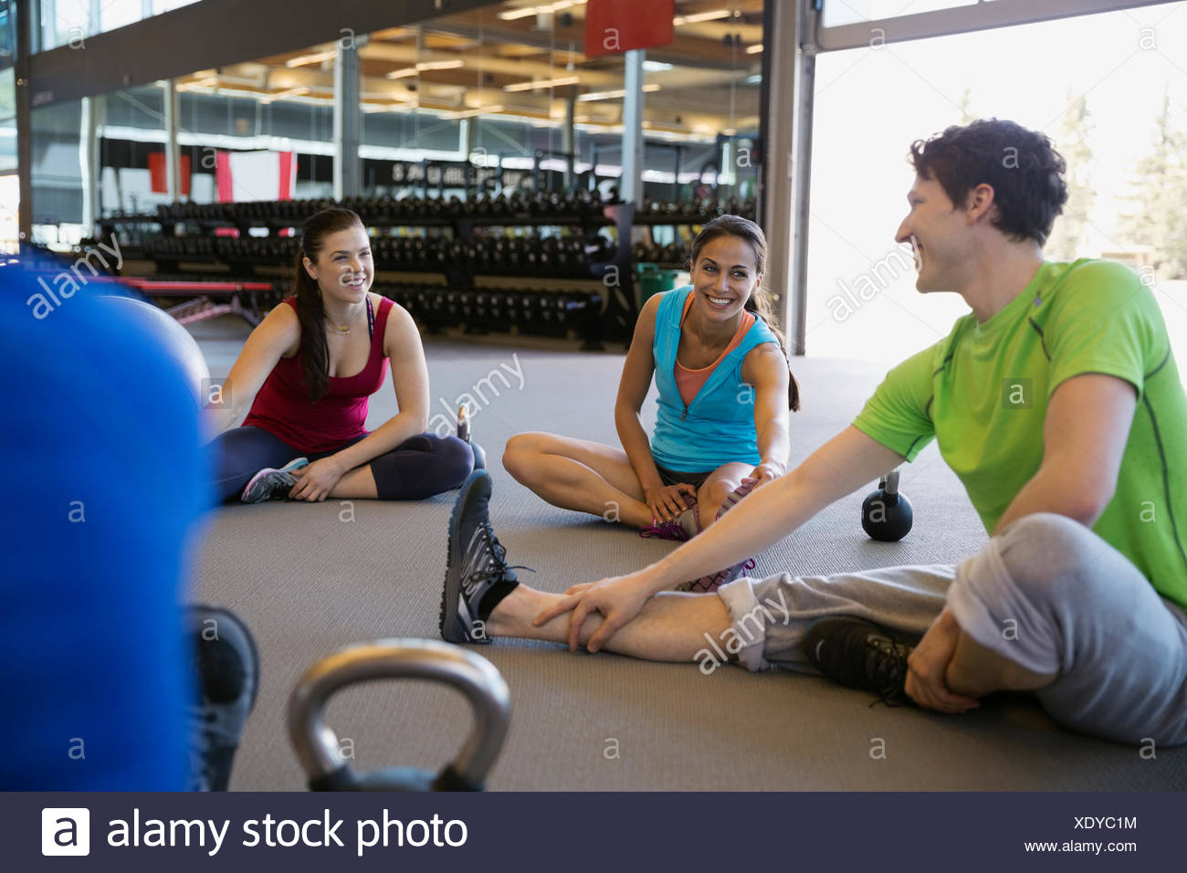 Exercise class stretching hamstrings in gym - Stock Image