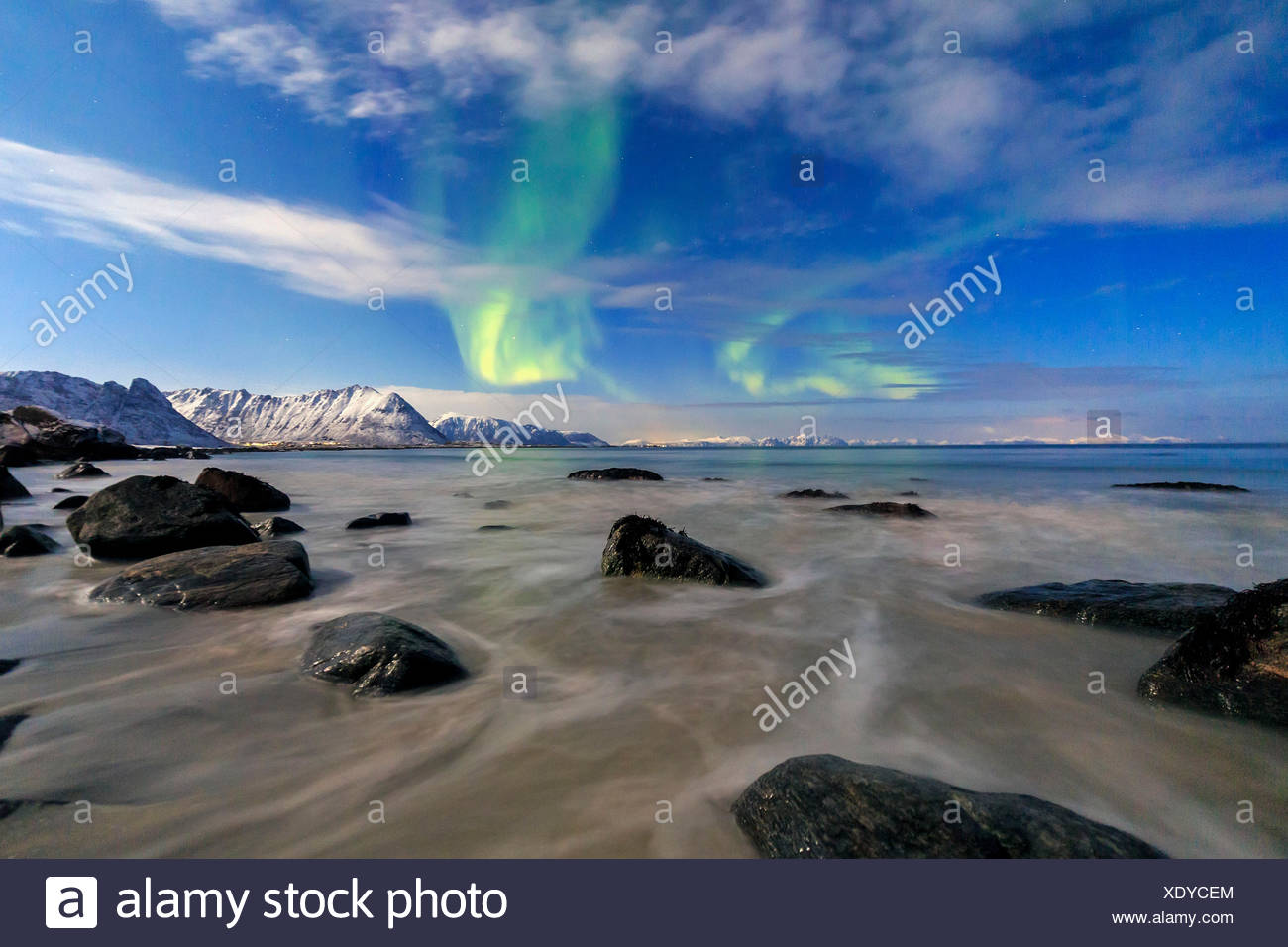 Northern Lights illuminate the landscape around Gymsøyand and the snowy peaks. Lofoten Islands Northern Norway Europe - Stock Image