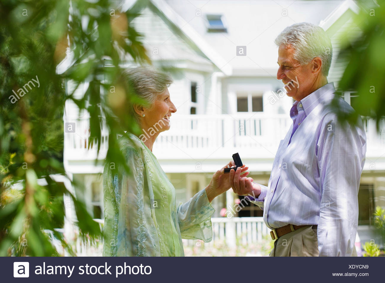 Senior man proposing to senior woman in summer garden near house smiling profile - Stock Image