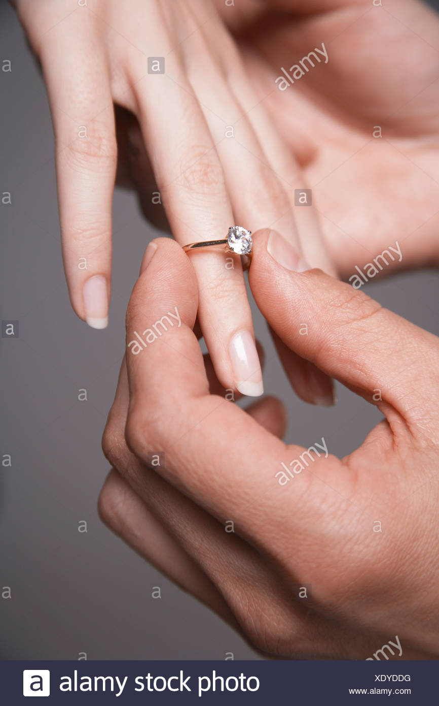 Man placing engagement ring on woman\'s finger, close-up of hands ...