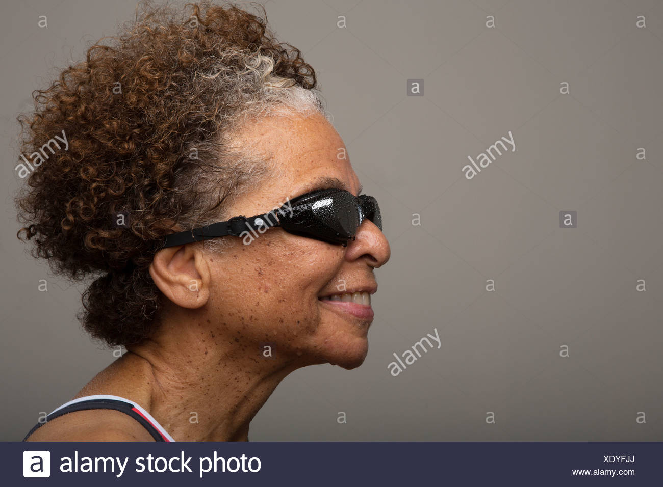 Studio portrait of senior woman in swimming goggles - Stock Image