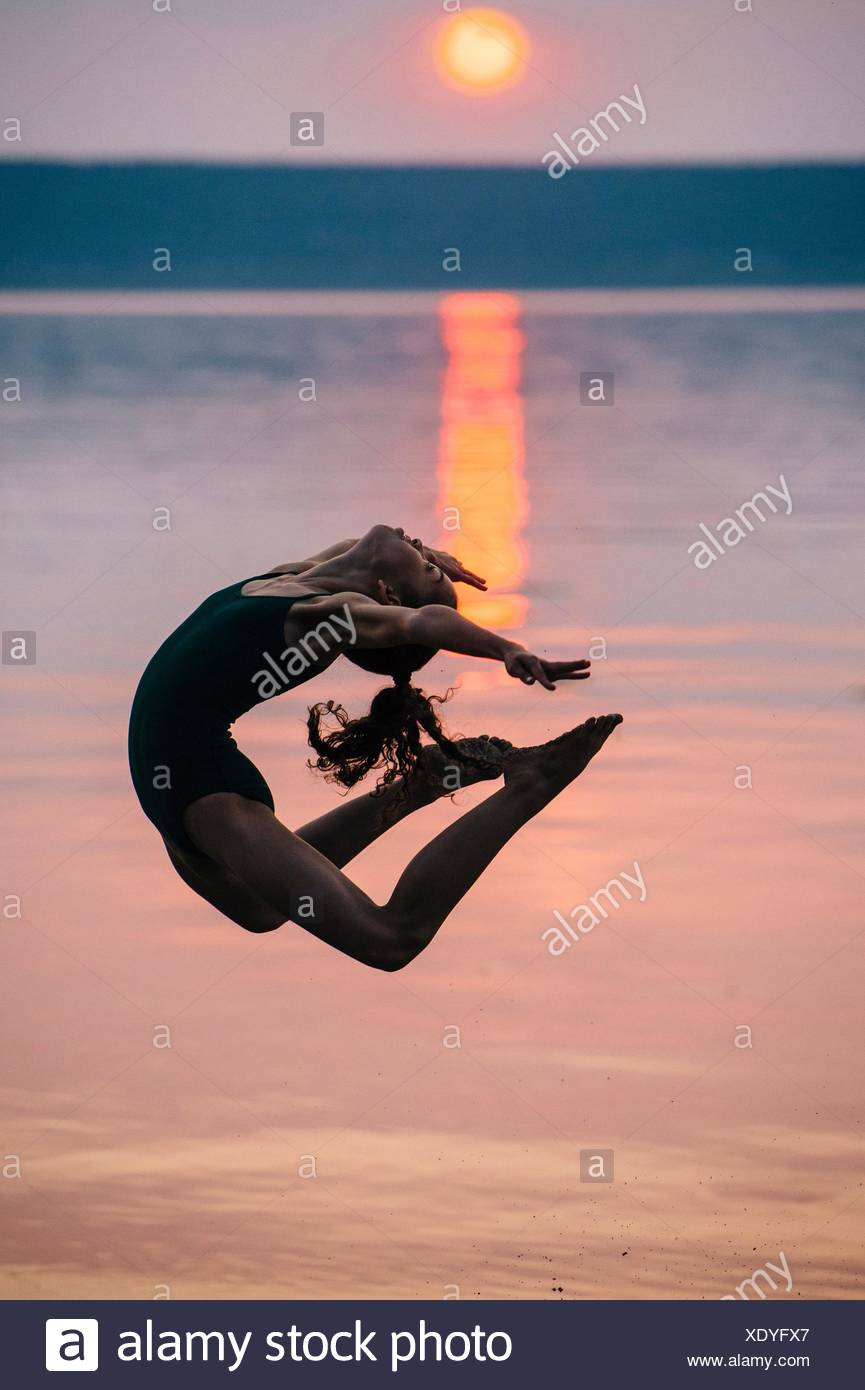 Side view of girl by ocean at sunset, leaping in mid air bending backwards Stock Photo
