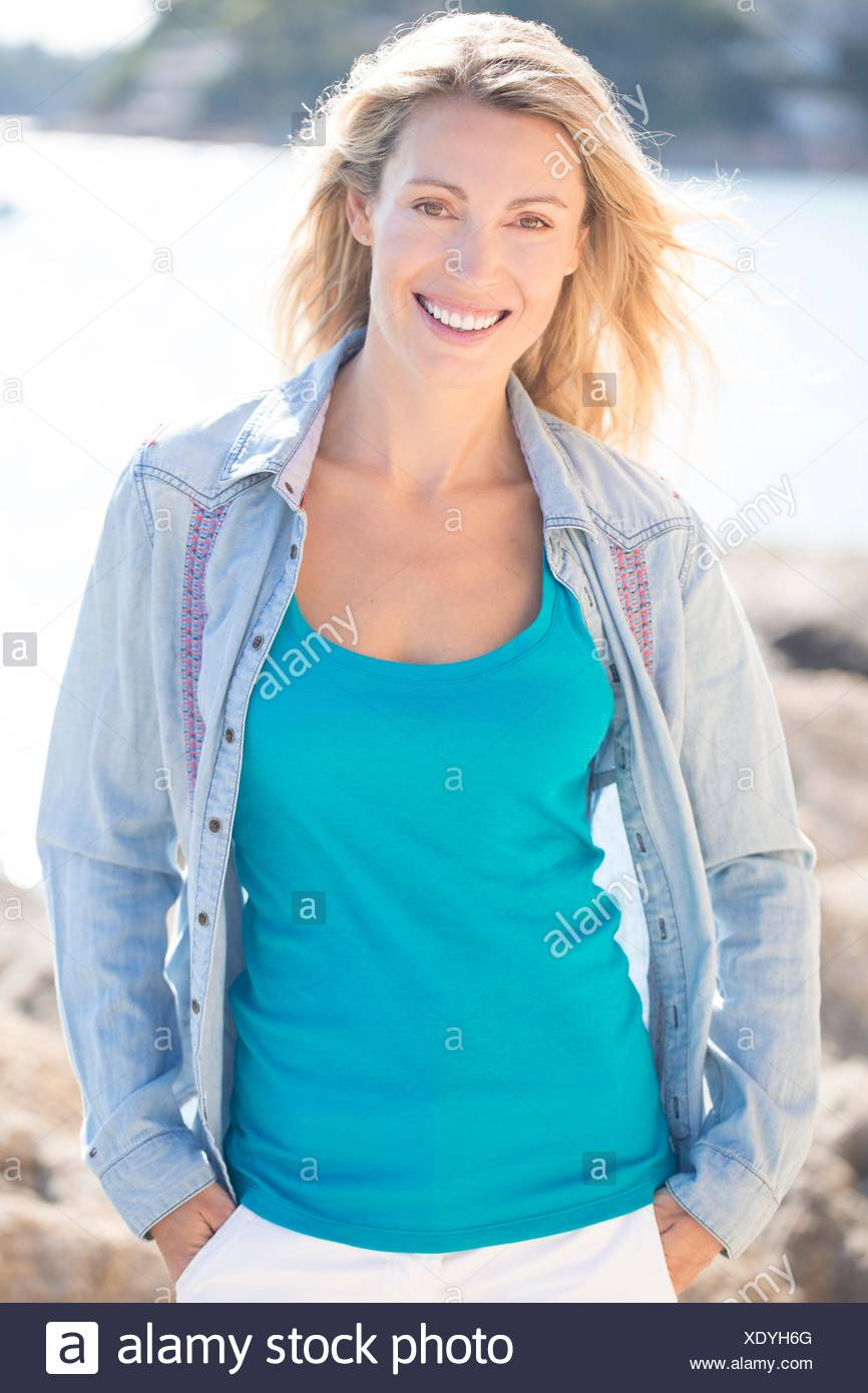 Portrait of smiling woman with denim shirt - Stock Image