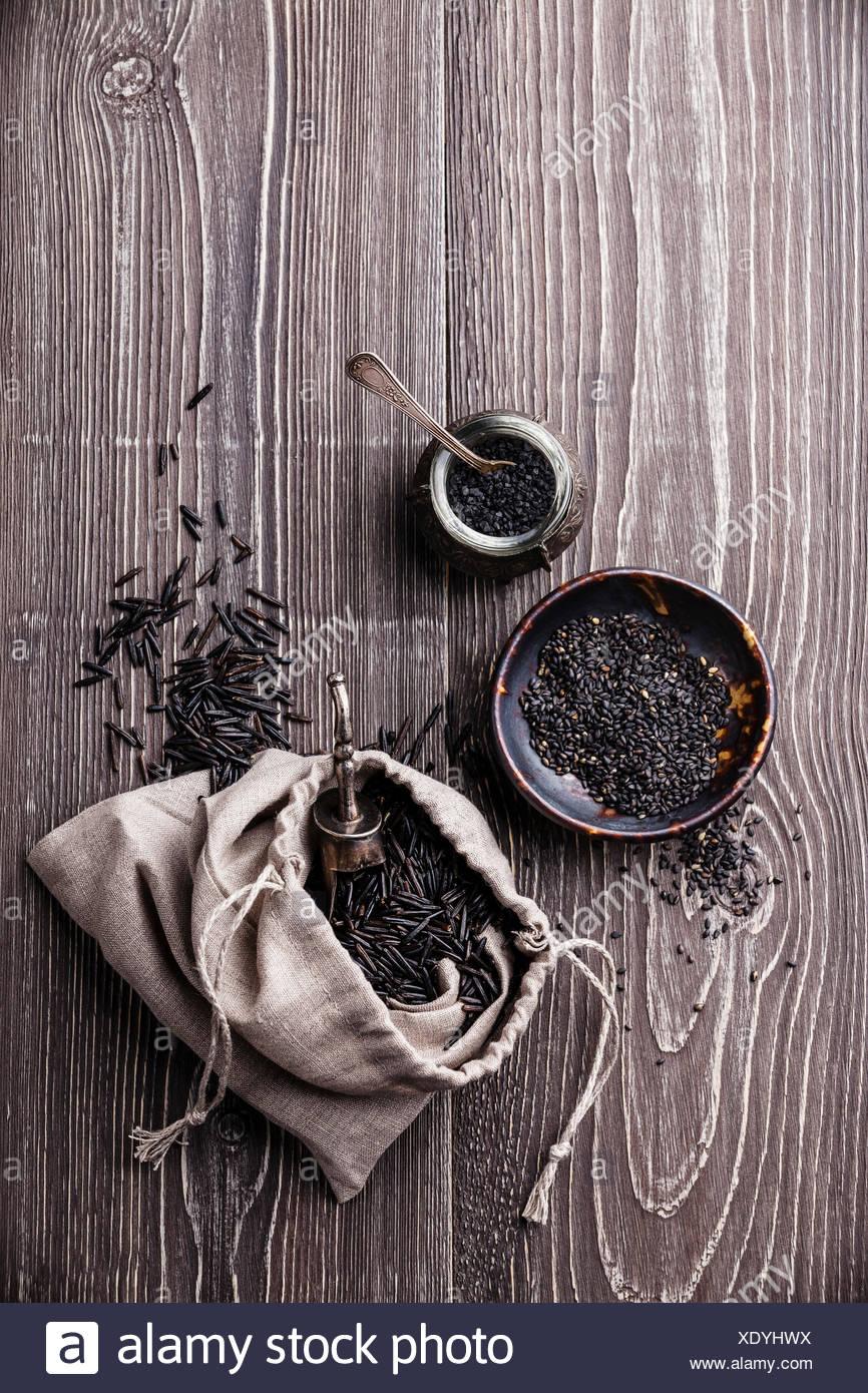 Black raw food ingredients - wild rice, sesame seeds, black salt on gray wooden background - Stock Image