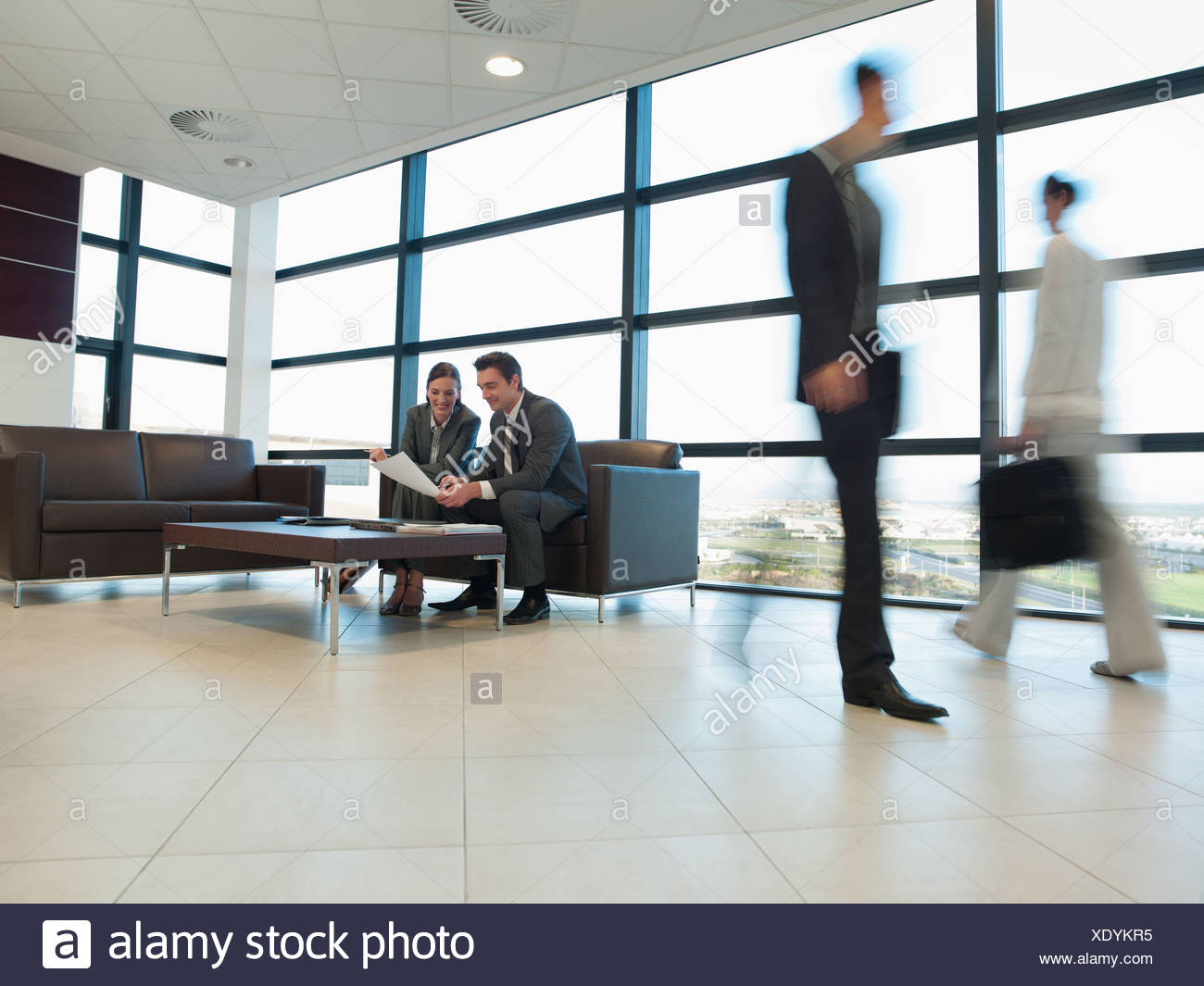 Business people working together in office waiting area - Stock Image