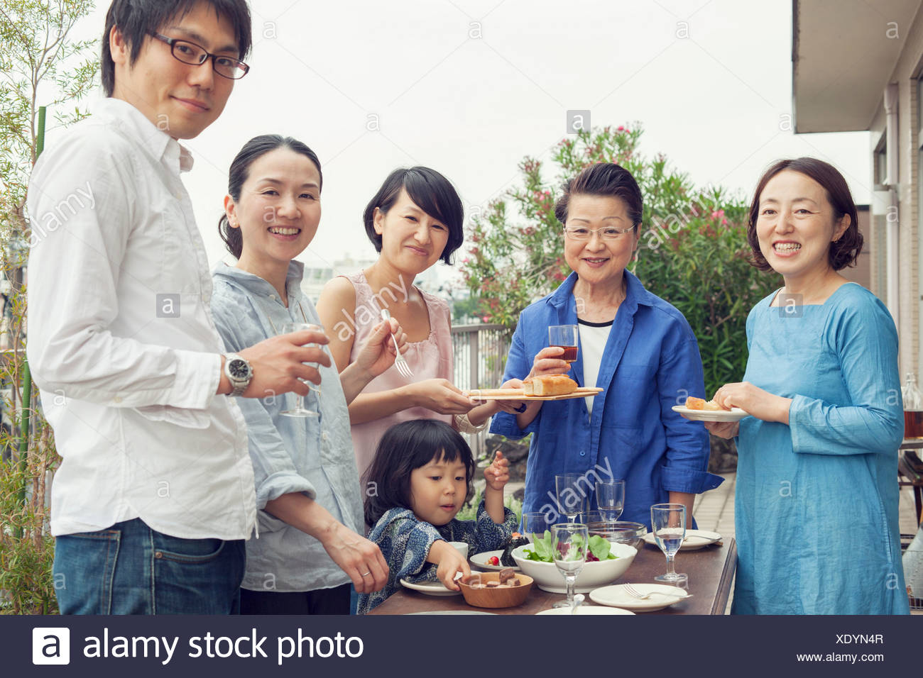 Three generation family eating outdoors, portrait - Stock Image