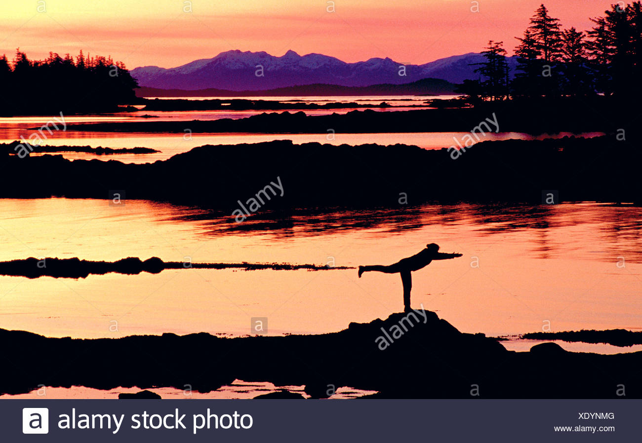Woman doing yoga on a rocky beach, Duke Island, Southeast, Alaska - Stock Image