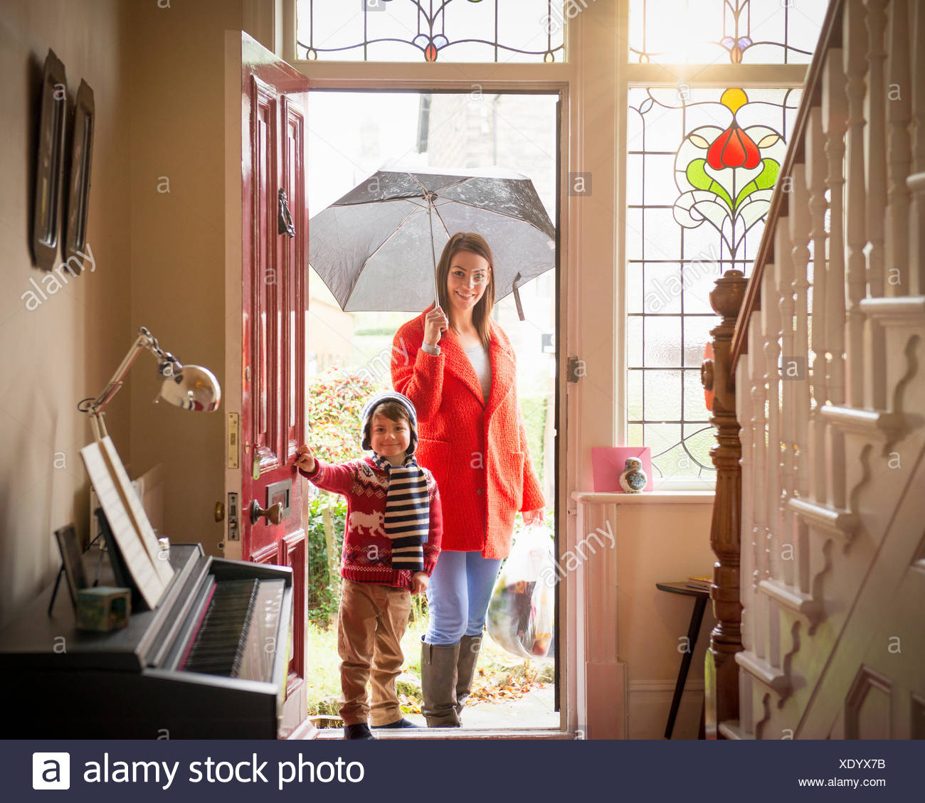 Mother and son arriving at front door of home on rainy day, portrait - Stock Image