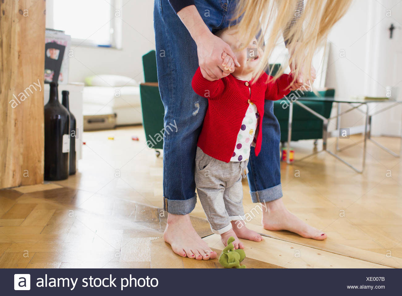 Baby girl holding mothers hands to take first steps - Stock Image