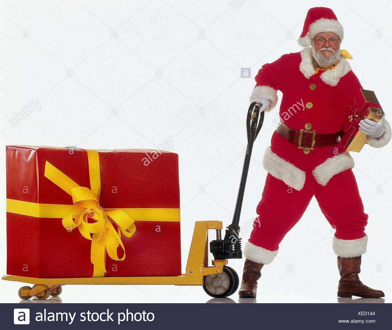Santa Claus, elevating platform truck, package, present, drag X-mas, Christmas, Santa, glasses, smile, Christmas present, Christmas presents, present, Christmas package, package, carry, deliver, delivery, deliver, distribute, distribute, studio, cut outs - Stock Image