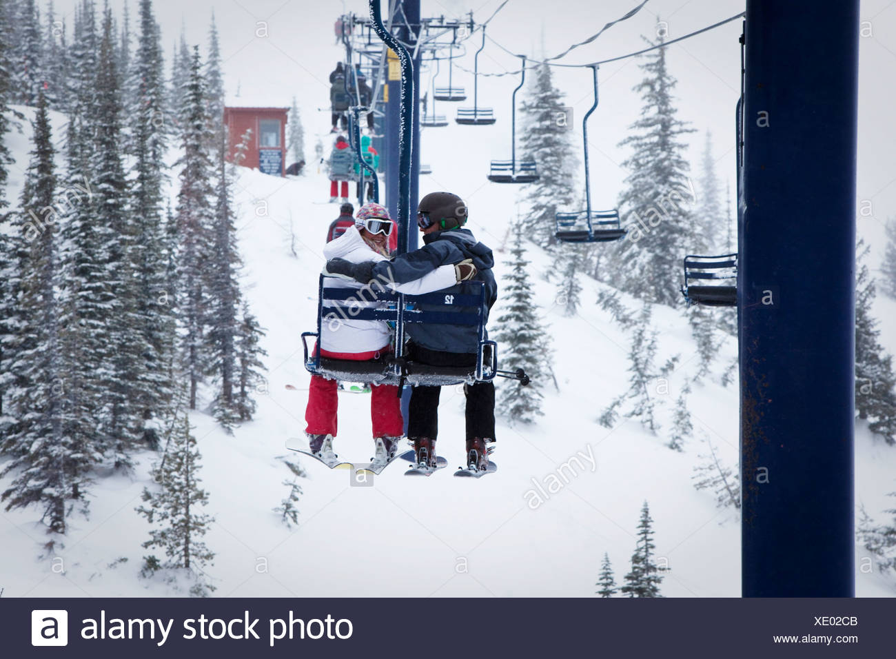 Two young adults smile while sitting on a double chairlift at a ski resort in Idaho. Stock Photo