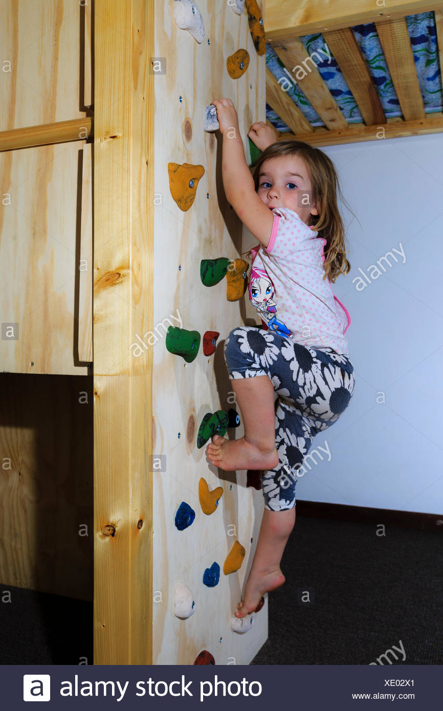 Girl, 3 years, climbing on a climbing wall in the children's room Stock Photo