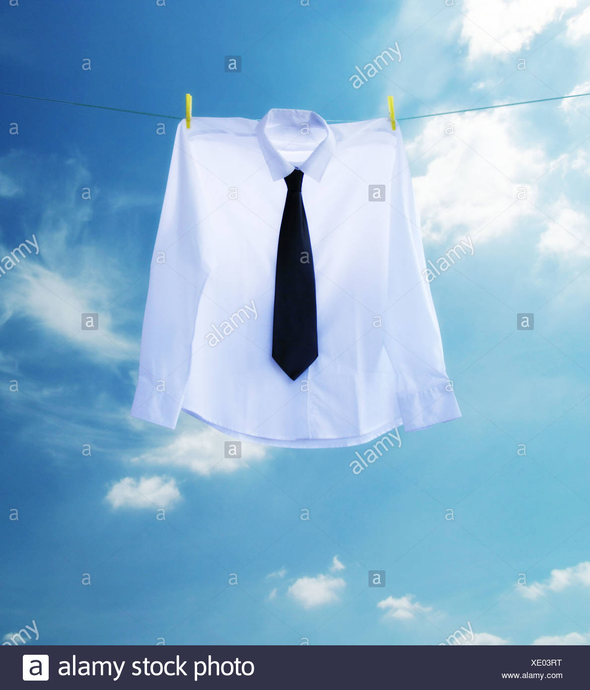 a shirt and tie handing on a washing line - Stock Image