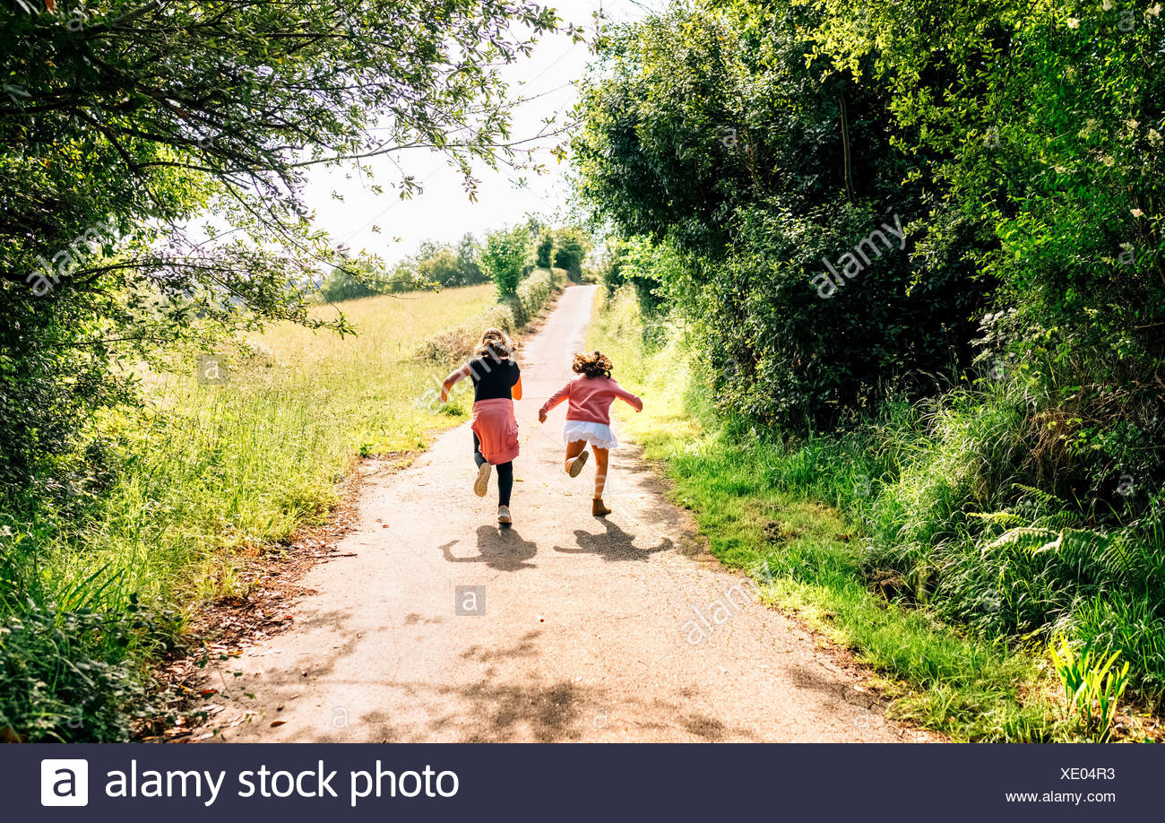 Two little girls running down a lane outdoors - Stock Image