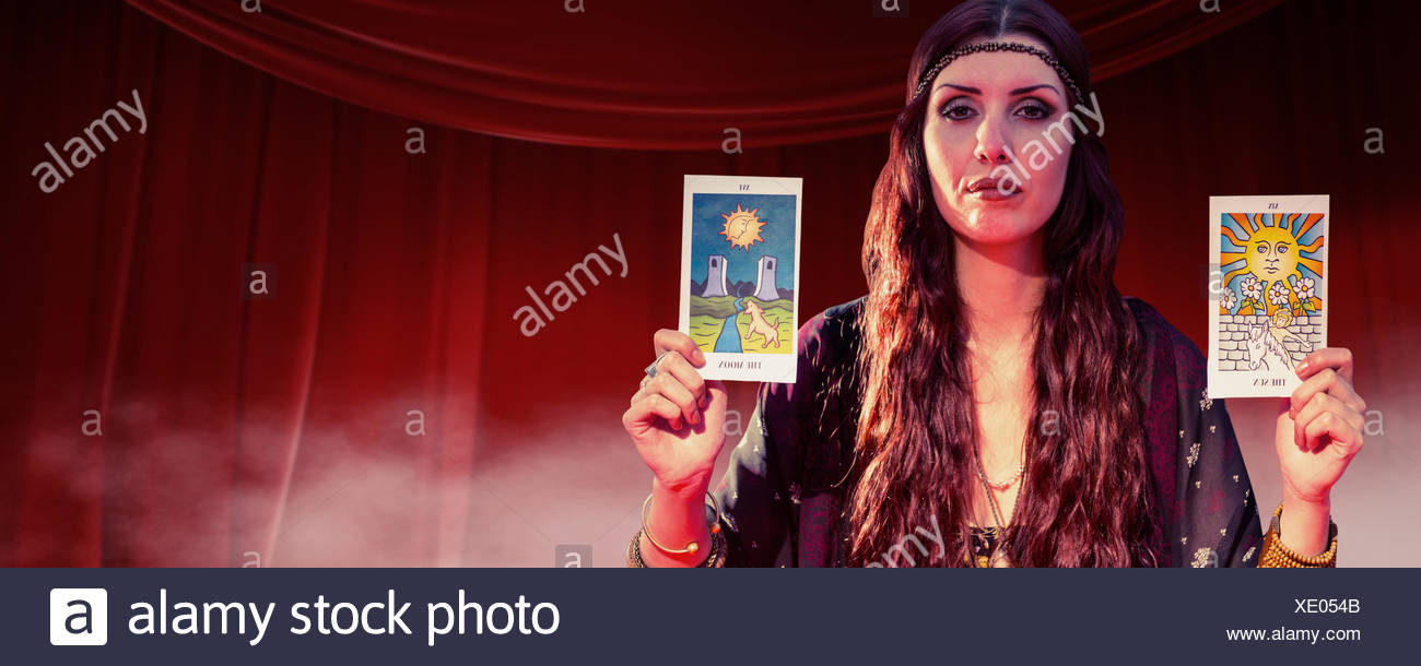 Composite image of portrait of fortune teller woman showing tarot cards - Stock Image