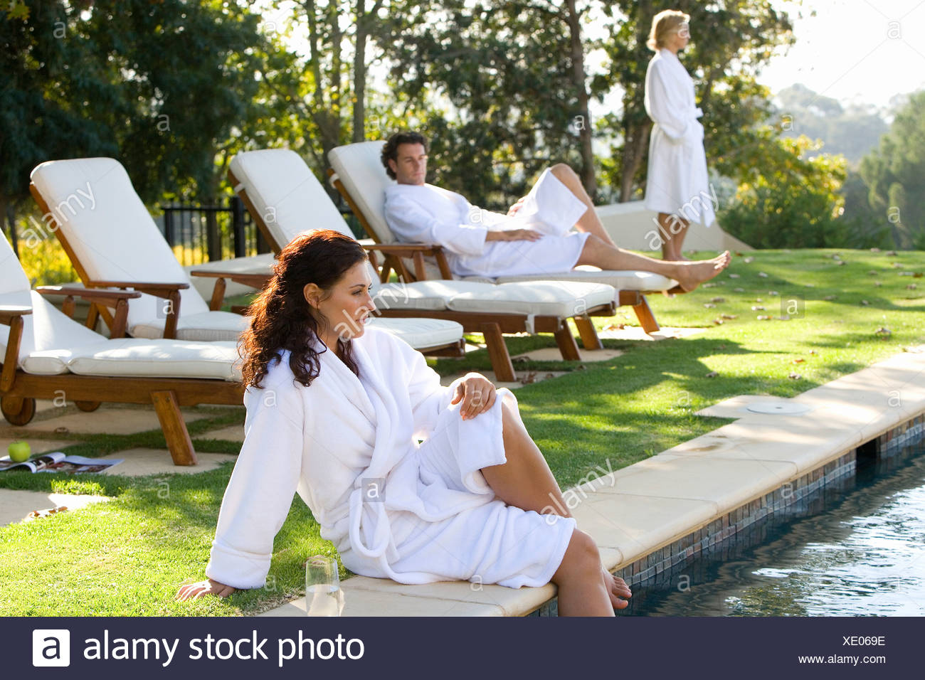 Young Woman Wearing White Robe Sitting By Swimming Pool With Legs In Water,  Man And Woman On Deck Chairs In Background