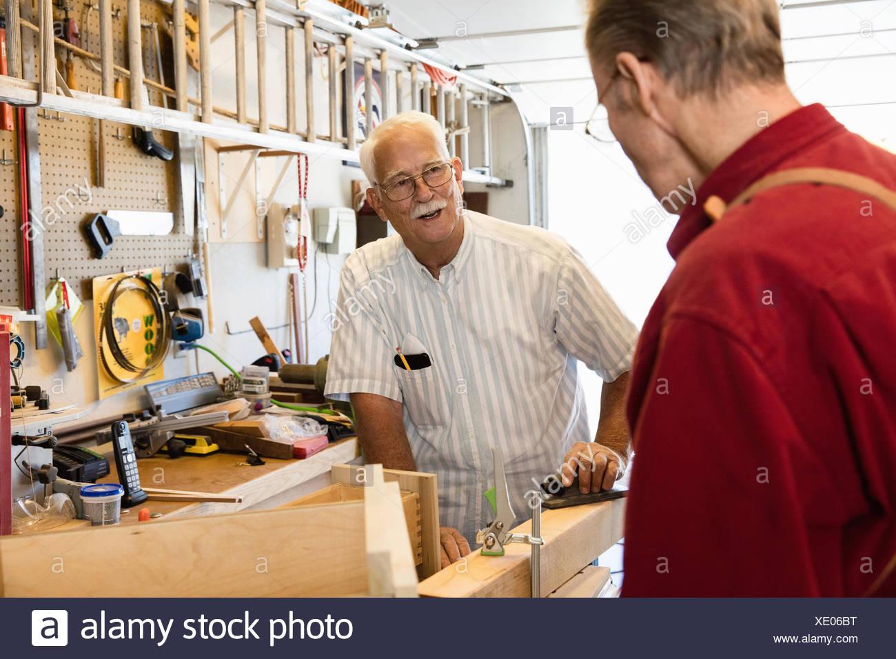 Senior men planing woodblock in carpentry workshop - Stock Image