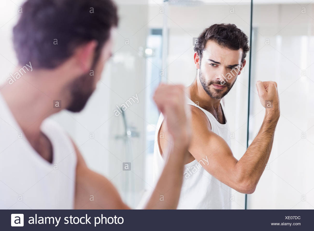 Smiling man looking at his biceps in mirror - Stock Image