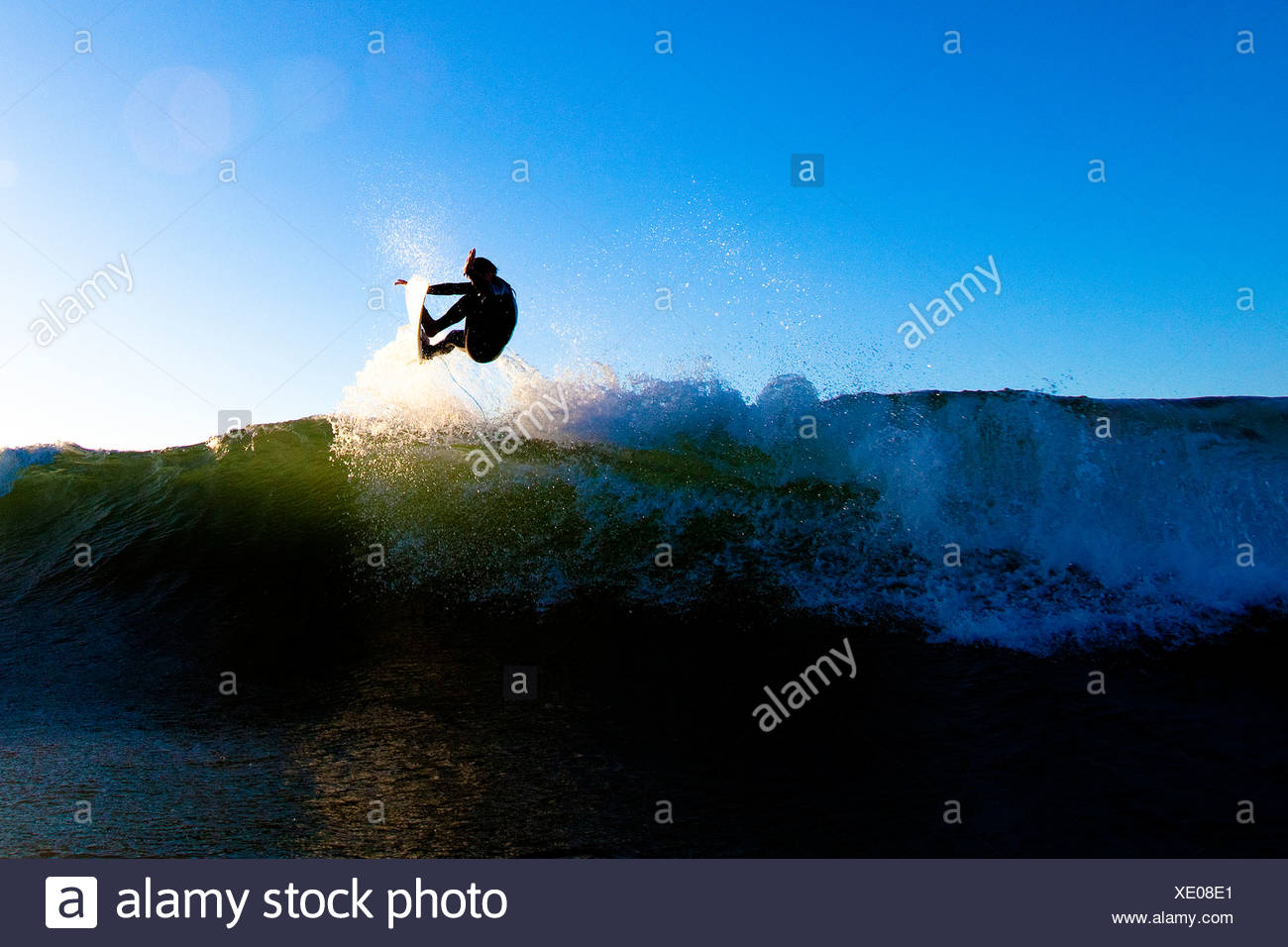 A skilled male surfer launches an air. - Stock Image