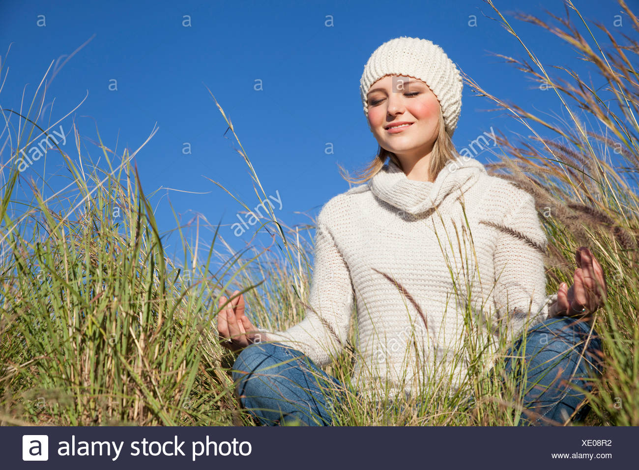 Young woman in yoga lotus position in long grass - Stock Image