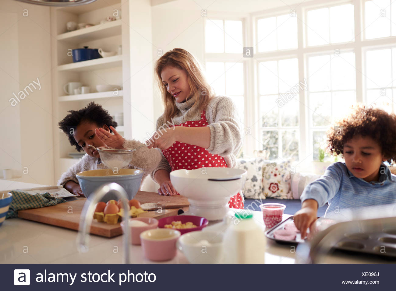 Mother Baking Cake With Children In Kitchen At Home Stock Photo