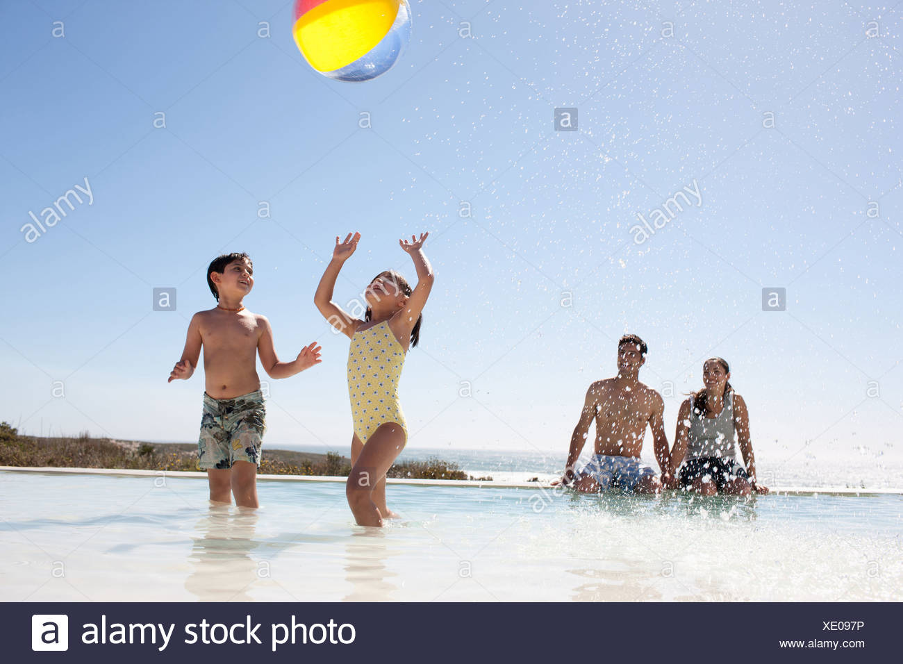 Family playing with ball in swimming pool - Stock Image