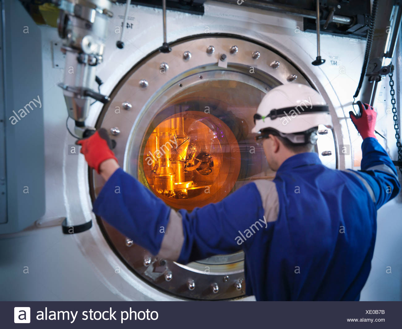 Engineer with fuel rod handling machine in nuclear power station - Stock Image