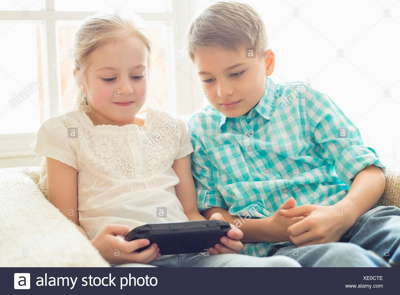 Siblings playing hand-held video game at home - Stock Image