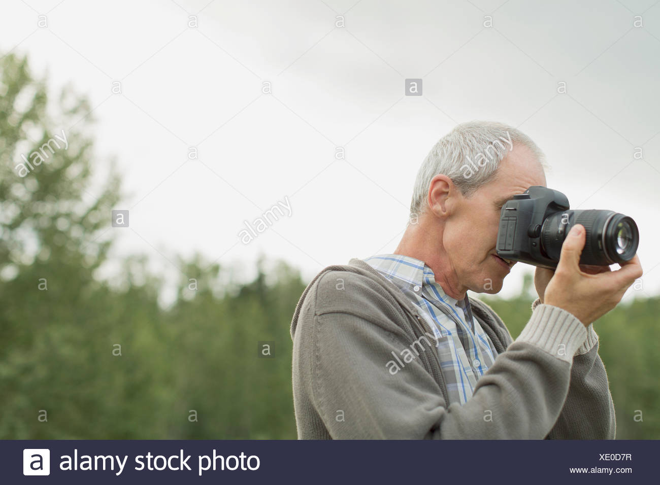 Middle-aged man taking pictures outdoors. - Stock Image