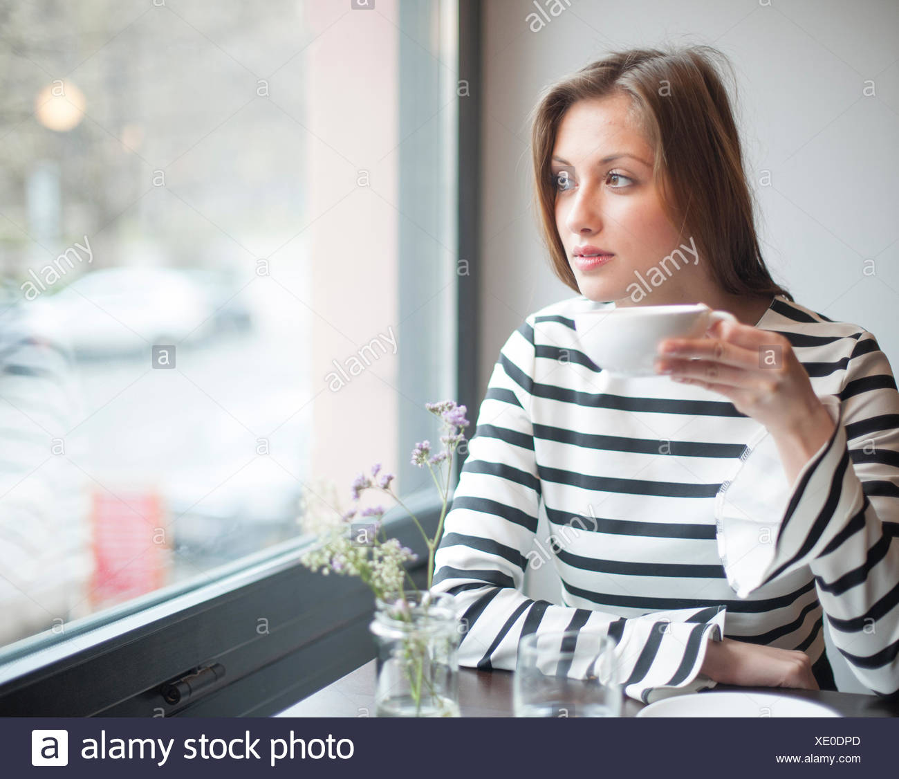 Thoughtful young woman looking out from window while drinking coffee in cafe - Stock Image