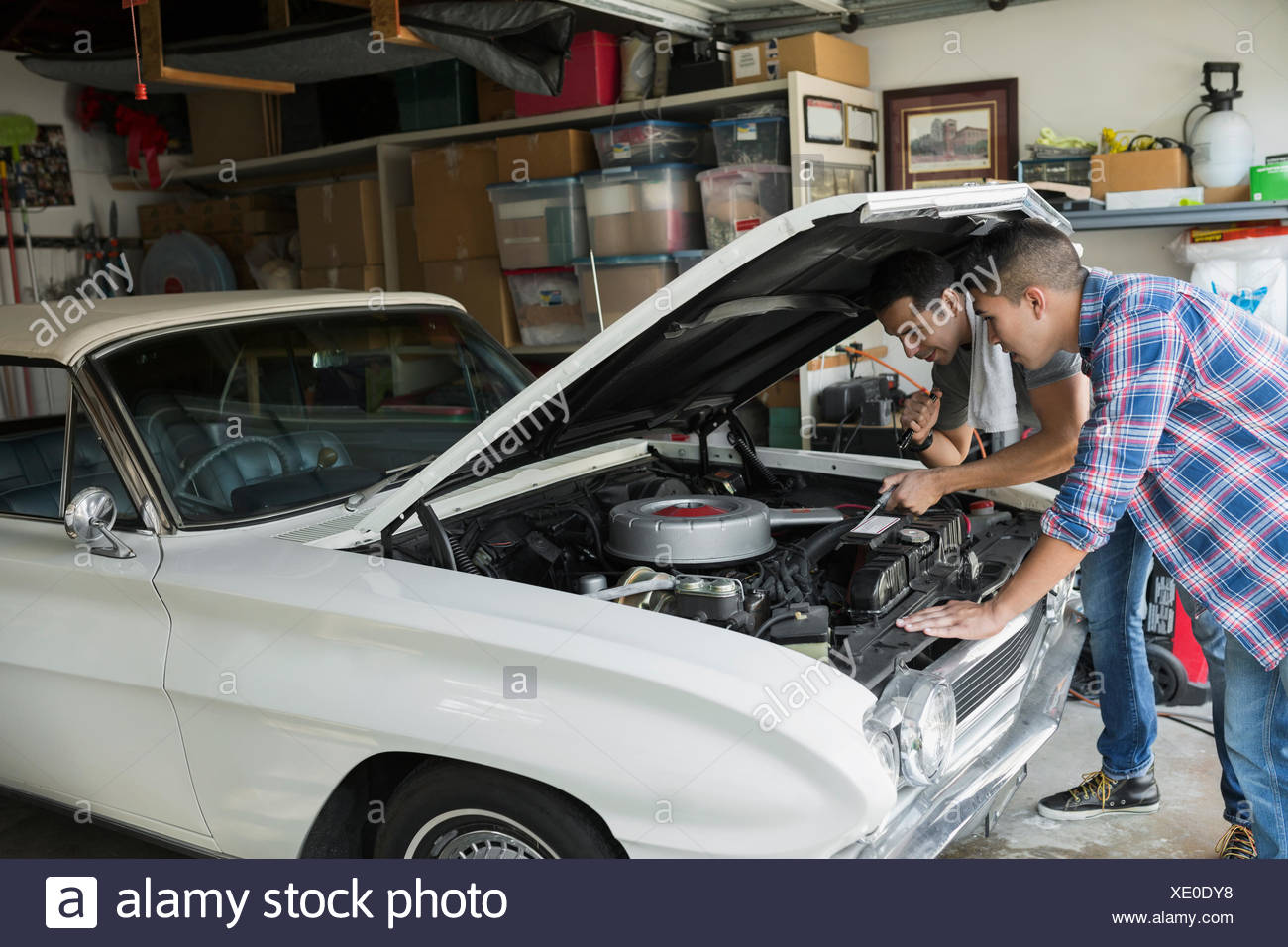 Father and son restoring vintage car engine garage - Stock Image